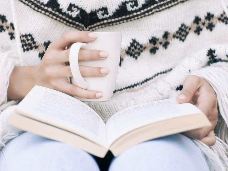 woman reading a book while holding a mug of tea or coffee