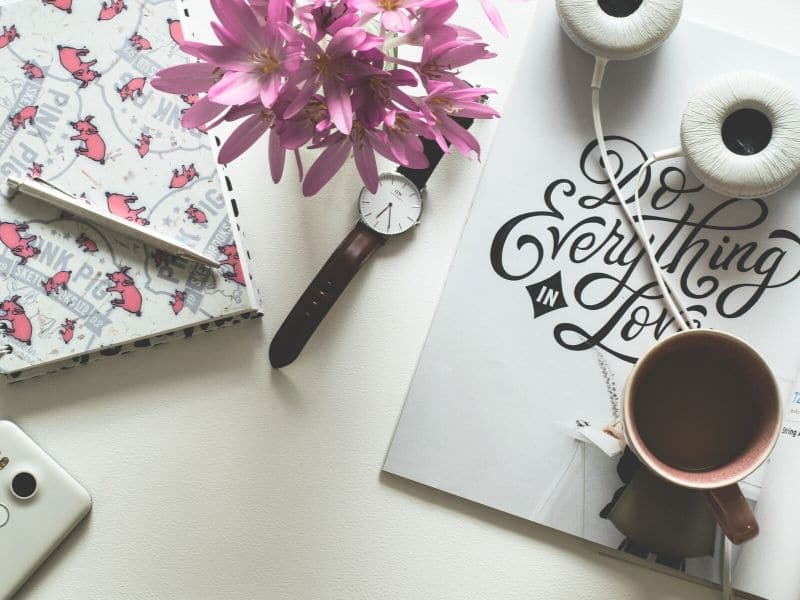 view of desk with notebook, watch, pen and coffee