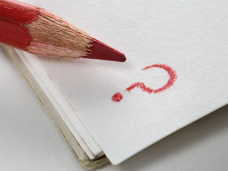 pencil writing question mark on paper
