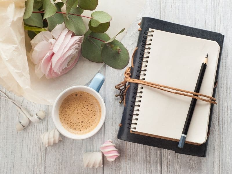 notebook, pencil, coffee, flowers on desktop