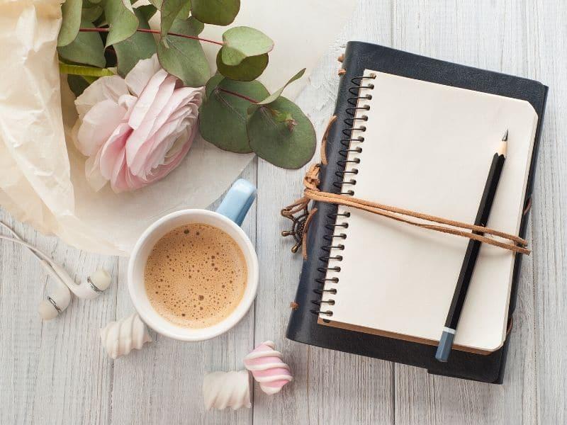 notebook, pencil, coffee, flowers on desktop