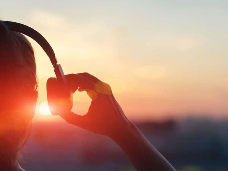 woman with headphones looking into sunset