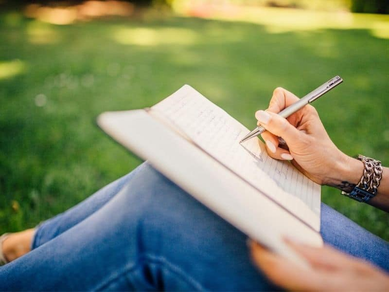 woman sitting outdoors writing in notebook
