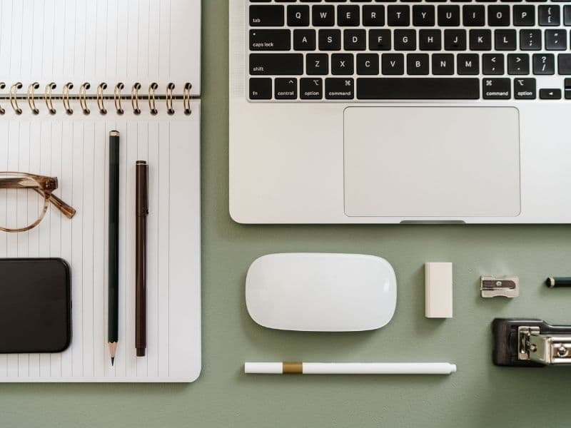 desk with computer, phone, notebook and pens