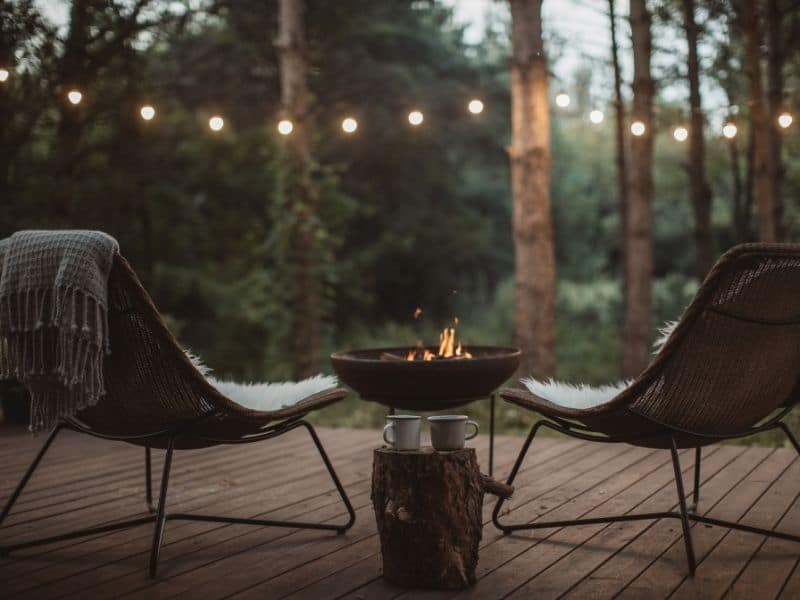 hygge cozy outdoor chairs, fire pit and warm drink
