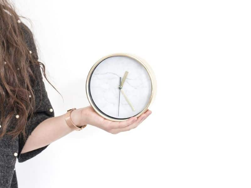 intentional time management - woman holding clock