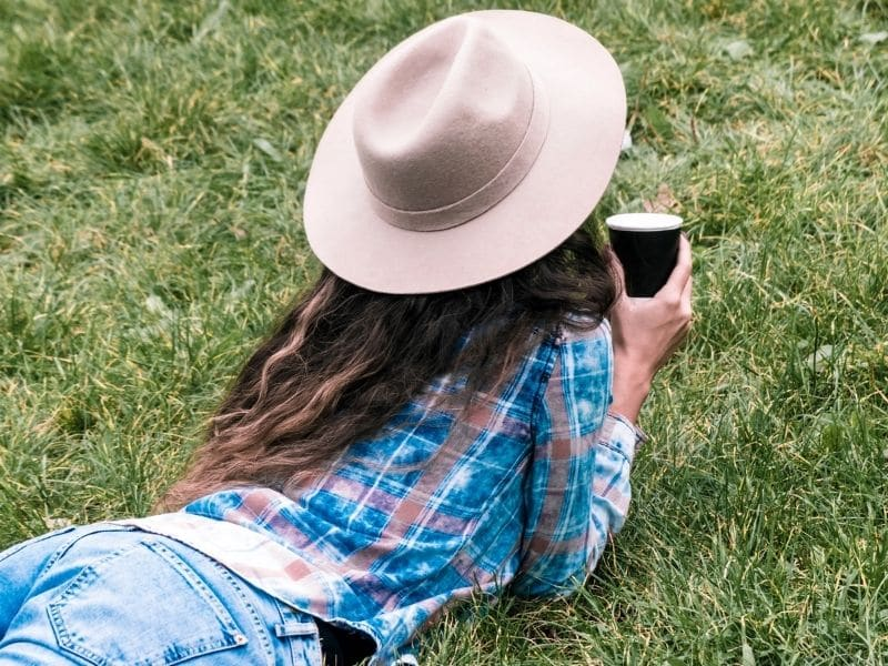 woman resting on grass drinking coffee